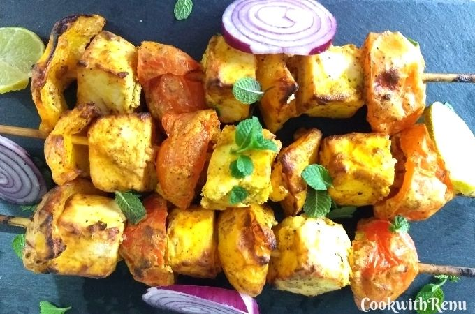 Paneer Tikka served on a black cheese board with onion and lemon wedges on the side