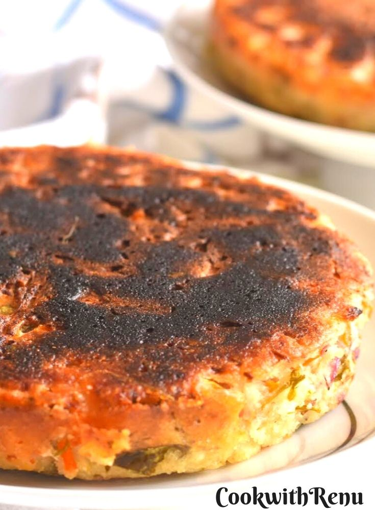 Close up look of the texture of Savoury Luni Poda Pitha, served on a plate, with crispy top and edges