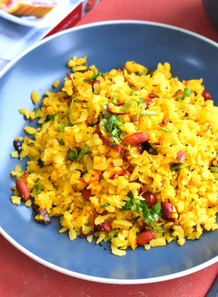 Kanda poha served in a blue plate. Seen in the background is a book