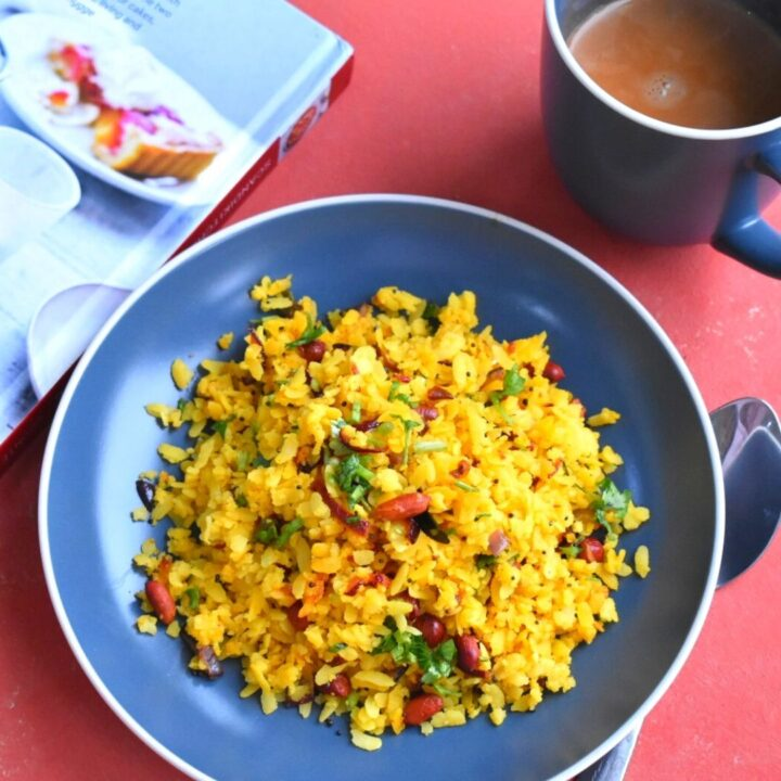 Kanda poha served in a blue plate. Seen in the background is a cup of tea and a book