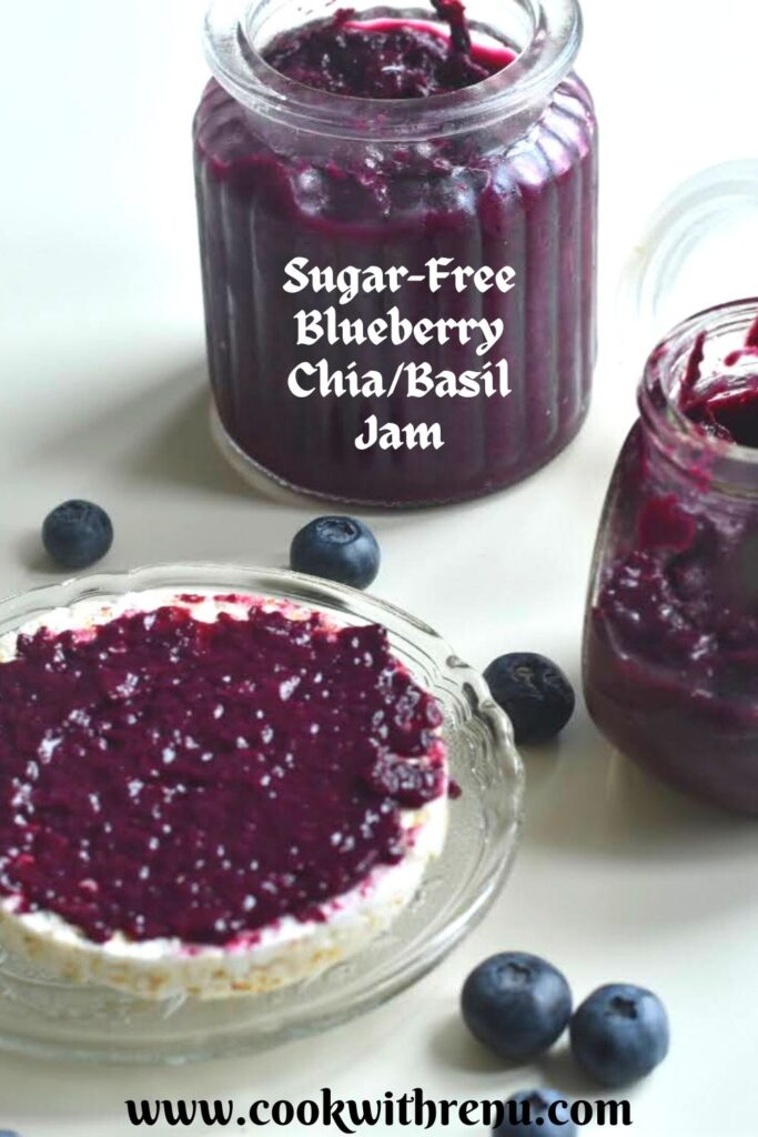 Blueberry chia jam spread on a rice cracker. Seen are 2 bottles of jar filled with jam along with some berries spread across.