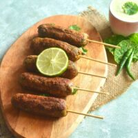 Farali Raw Banana Kebab arranged on a wooden board with a garnish of lemon. Seen along side is a dip served along with chillies