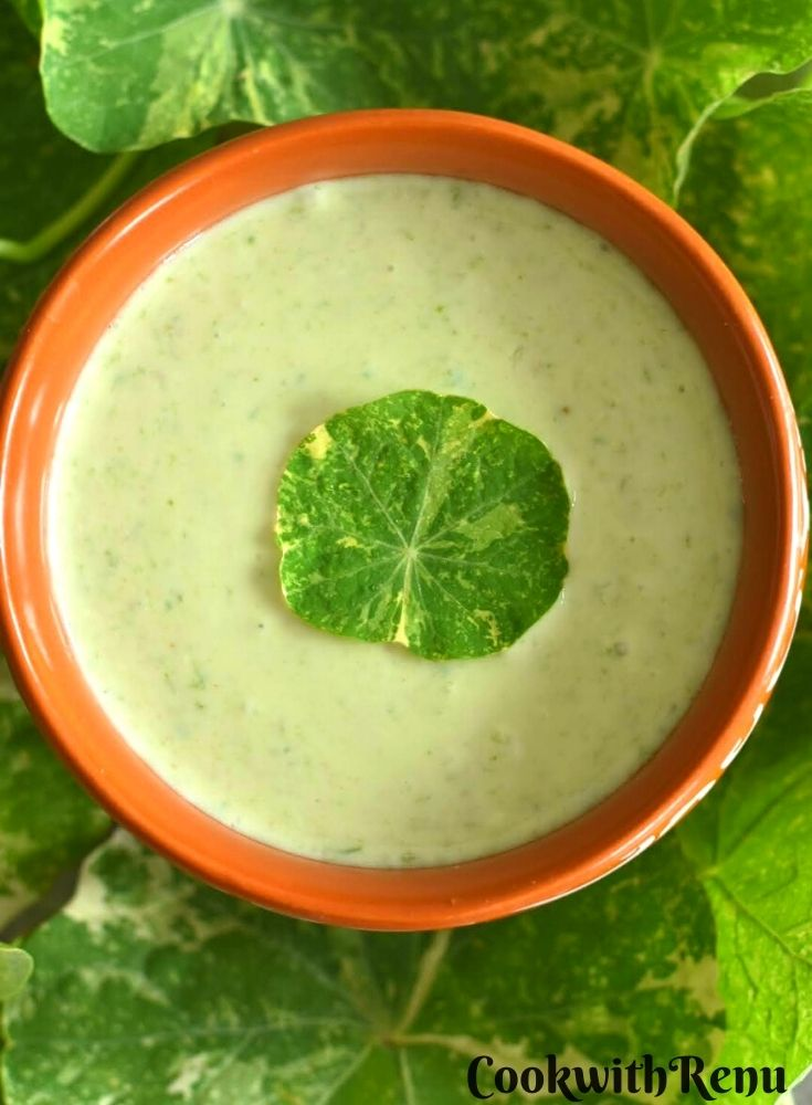 Clouse up look of Nasturtium Leaves & Stems Raita served in a brown bowl with some leaves scattered around