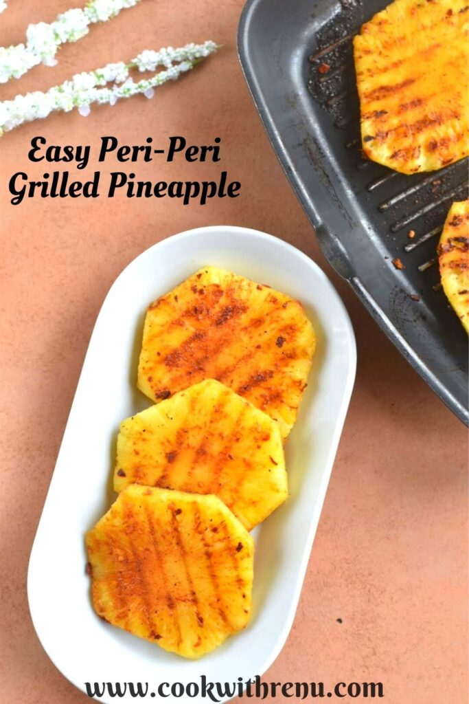 Peri Peri Grilled Pineapple served on a white plate. Seen in the background is a grill pan with pineapple.