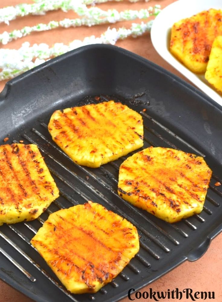 Peri Peri Grilled Pineapple on a grilled pan and seen in the background are more pineapple slices