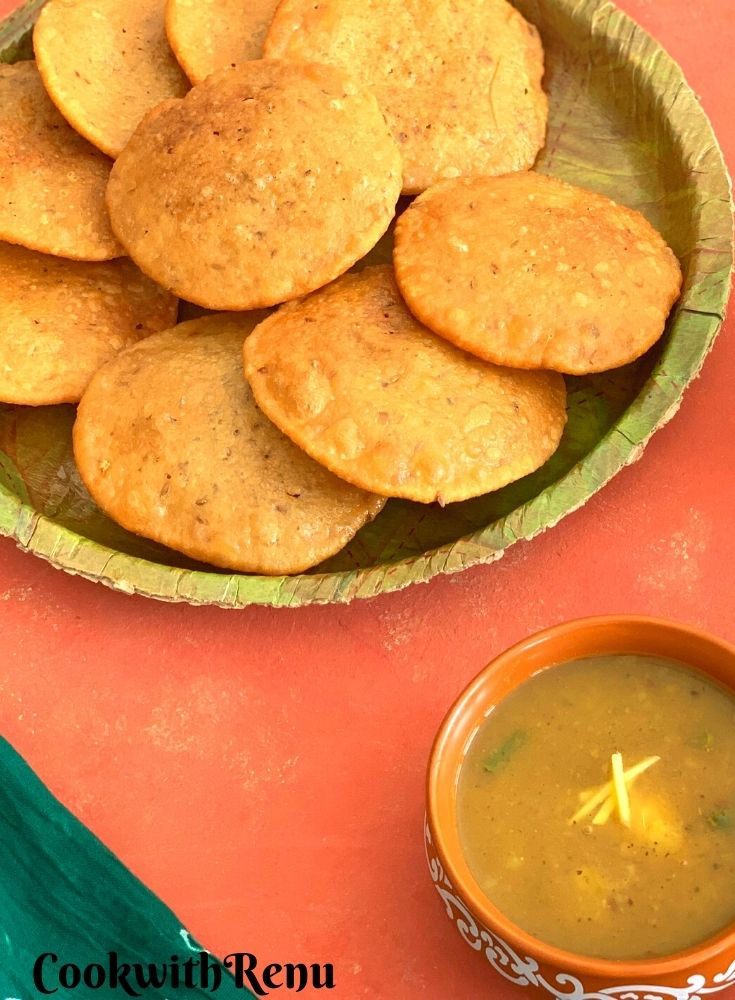 A plate served with crispy bedais. Seen in the background is a bowl of aloo saag