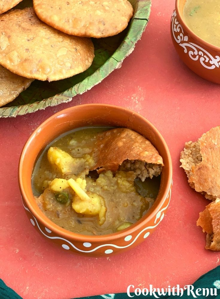 A piece of bedai dunked in mathura ke dubki wale aloo in a brown bowl. seen along side are some crispy puris.