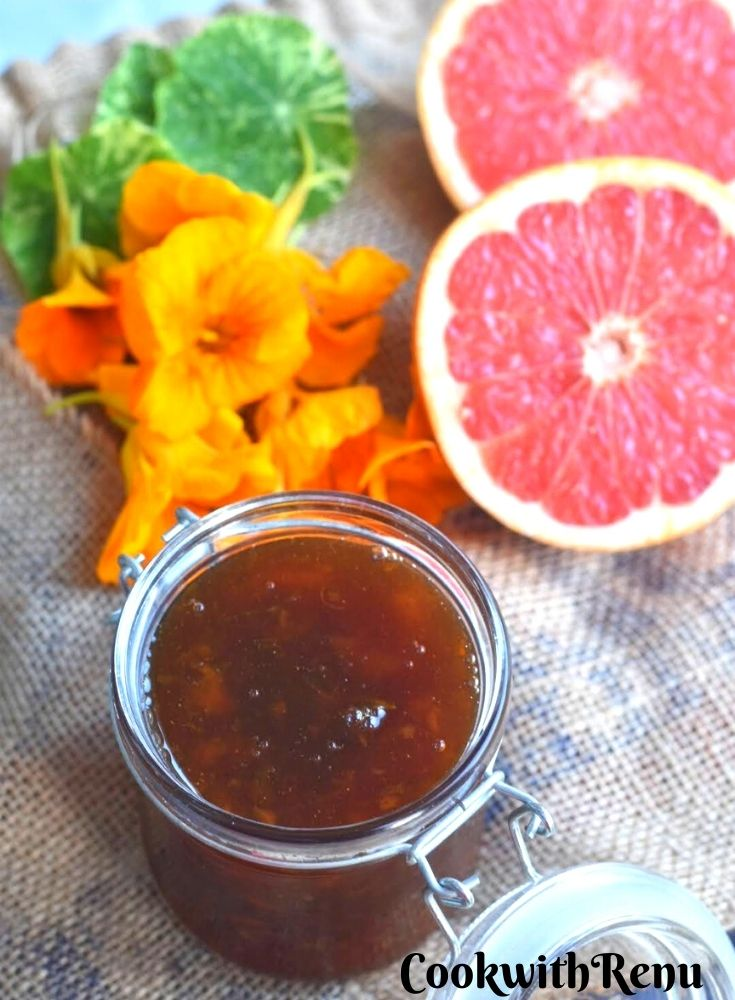 Nasturtium and Grapefruit Marmalade in a glass jar, seen along side is a cut Grapefruit and some Nasturtium flowers and leaves