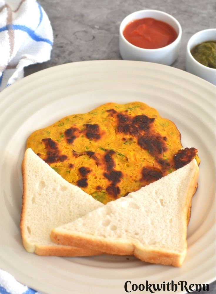 Vegan Chickpea Tomato Omeletee served with a bread slice along with tomato ketchup and green coriander chutney