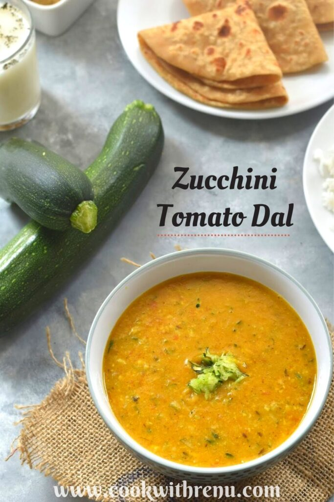 Zucchini dal served in a white bowl along with hot steaming white rice and some roti