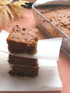 Apple brownies stacked one above the other. Seen along side is a tray of baked apple brownie along with some flowers.
